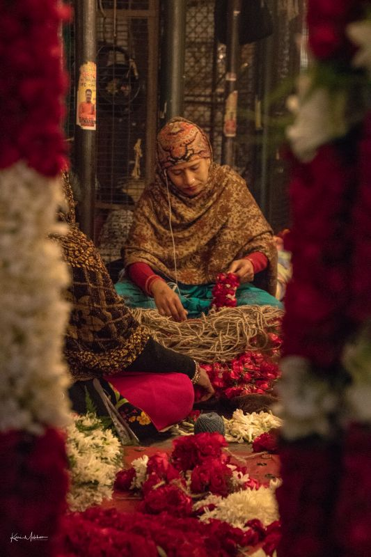 A woman making garlands in the flower market